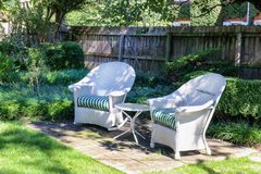 Två antika vita vide- stolar som är ordnade med tabellen i skuggig fläck i landskap gård i exklusiv stads- grannskap jpg arkivfoto