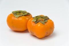 Två aptitretande persimmons som isoleras på white Royaltyfria Foton
