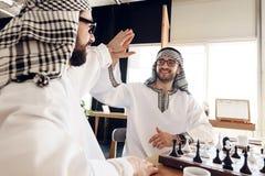 Två arabiska affärsmän höga fem bak schackbrädet på hotellrum arkivbild