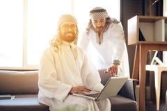 Två arabiska affärsmän med bärbara datorn på soffan på hotellrum royaltyfri foto