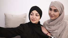 Två arabiska kvinnor i hijabs som sitter på den gråa soffan, medan ta selfiebilden tillsammans hemma Vit vägg på lager videofilmer