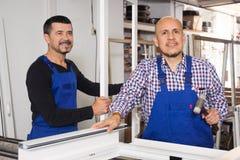 Två arbetare gjorde dörrar Fotografering för Bildbyråer