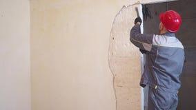 Två arbetare i skyddande dräkt demolerar murbrukväggen lager videofilmer