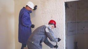 Två arbetare i skyddande dräkt demolerar murbrukväggen stock video