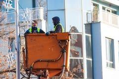 Två arbetare installerar julgarnering på höjd Fotografering för Bildbyråer