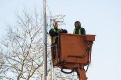Två arbetare installerar julgarnering på höjd arkivfoto