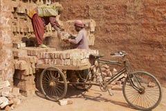 Två arbetare laddar cykeln med tegelstenar i Dhaka, Bangladesh royaltyfria foton