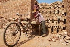 Två arbetare laddar cykeln med tegelstenar i Dhaka, Bangladesh Royaltyfri Bild