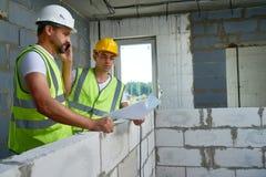 Två arbetare med golvplan Arkivfoto