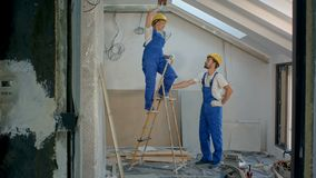Två arbetare med stegen, medan göra reparationer till byggande arkivfilmer