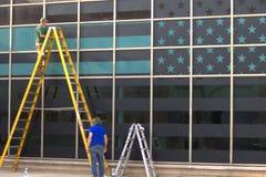 Två arbetare och en flagga i fönstret Royaltyfri Foto