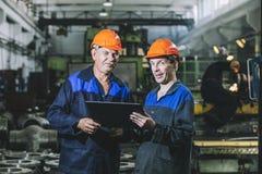 Två arbetare på en industrianläggning med en minnestavla i handen, workin arkivfoto