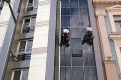 Två arbetare som gör ren fönster på hög löneförhöjningbyggnad Arkivfoton