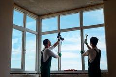 Två arbetare som installerar ett fönster royaltyfria bilder