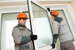 Två arbetare som installerar fönstret arkivbild