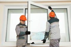 Två arbetare som installerar fönstret arkivfoto