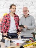 Två arbetare som ser räknemaskinen i studio royaltyfri bild