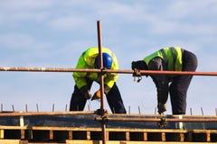 Två arbetare som sticker stänger för metallstänger in i ramförstärkningen royaltyfria foton