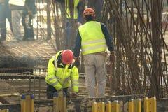 Två arbetare som sticker stänger för metallstänger in i ramreinforcemen Arkivbild