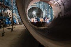 Två arbetare som svetsar i fabriks- kokkärl för en fabrik Royaltyfria Bilder