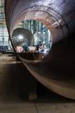 Två arbetare som svetsar i fabriks- kokkärl för en fabrik Arkivbild