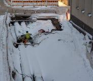 Två arbetare som svetsar på ett stort rör bland det insnöat en stads- konstruktionsplats, Helsingfors Finland royaltyfria bilder