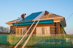 Två arbetare täcker taket av ett lantligt hus med metalltegelplattor royaltyfri bild