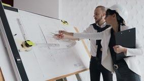 Två arkitekter arbetar på ett nytt privat husprojekt Bild av projektet på ritbordet Teamwork arkivfilmer