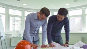 Två arkitekter arbetar på projektet på kontoret arkivfilmer