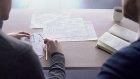 Två arkitekter arbetar tillsammans på byggnadsritningar på tabellen stock video