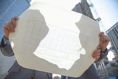 Två arkitekter på en ritning för innehav för konstruktionsplats Arkivfoto