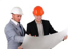 Två arkitekter som har gyckel som diskuterar ett plan Royaltyfri Bild