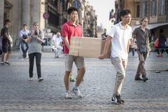 Två asiat som bär den stora kartongen i stadscentret Royaltyfri Fotografi
