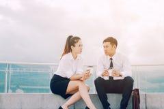 Två asiatiska affärspersoner som talar utanför företaget med att rymma c royaltyfri bild