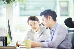 Två asiatiska affärspersoner som tillsammans i regeringsställning arbetar royaltyfri foto