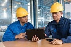 Två asiatiska arbetare som inomhus analyserar information royaltyfri foto