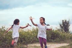 Två asiatiska barn som spelar med leksakpappersairplanep Royaltyfri Foto