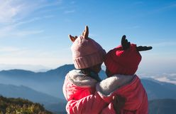 Två asiatiska barnflickor som bär tröjan och den varma hatten som kramar samman med förälskelse på den härliga misten och berget royaltyfria bilder