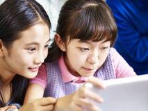 Två asiatiska elementära skolflickor som tillsammans använder den digitala minnestavlan Arkivfoton
