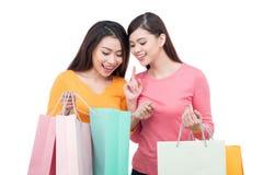 Två asiatiska flickavänner med shopping som isoleras på vit Fotografering för Bildbyråer