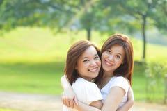 Två asiatiska flickor som har gyckel arkivfoton