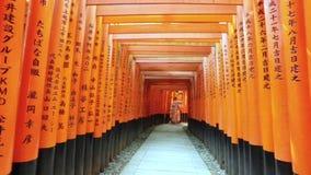 Två asiatiska flickor tar ett selfiefoto på den röda porten på shintorelikskrin arkivfilmer