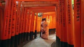Två asiatiska flickor tar ett selfiefoto på den röda porten på shintorelikskrin stock video