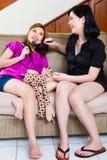 Två asiatiska indonesiska flickor returnerar genom att använda smink Arkivbilder