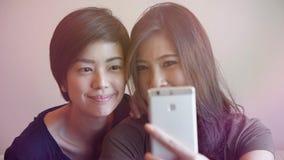 Två asiatiska kvinnor som tar fotoet, selfie genom att använda mobiltelefonen Royaltyfria Foton