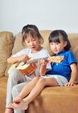 Två asiatiska lilla flickor som spelar ukulelet och tillsammans sjunger Fotografering för Bildbyråer