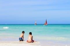 Två asiatiska pojkar som spelar på den vita sandiga stranden Royaltyfria Bilder