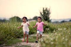 Två asiatiska små flickor som har gyckel och spring tillsammans Royaltyfri Foto