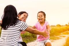 Två asiatiska små flickor som kör till deras moder för att ge en kram Fotografering för Bildbyråer