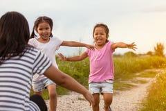 Två asiatiska små flickor som kör till deras moder för att ge en kram Royaltyfria Bilder